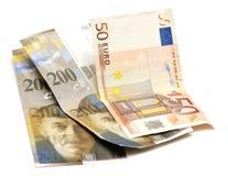 Los francos suizos y el euro Fotografía de archivo