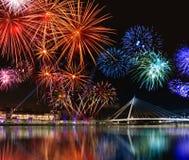 Los fuegos artificiales coloridos acercan al agua Imagen de archivo libre de regalías