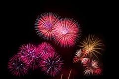 Los fuegos artificiales coloridos sobre el cielo nocturno, los fuegos artificiales rojos alinean Imagen de archivo