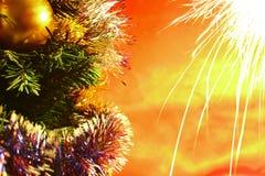 Los fuegos artificiales del día de fiesta acercan a decoraciones de la Navidad en el árbol con el fondo rojo Imágenes de archivo libres de regalías