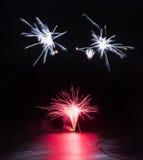 Los fuegos artificiales exhiben sobre el mar con reflexiones en agua Foto de archivo libre de regalías