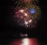 Los fuegos artificiales exhiben sobre el mar con reflexiones en agua Foto de archivo