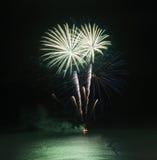 Los fuegos artificiales exhiben sobre el mar con reflexiones en agua Imagen de archivo libre de regalías
