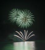 Los fuegos artificiales exhiben sobre el mar con reflexiones en agua Imagen de archivo