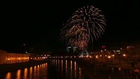 Los fuegos artificiales hermosos brillantes en la ciudad en el terraplén en el cielo nocturno se reflejan en el río metrajes