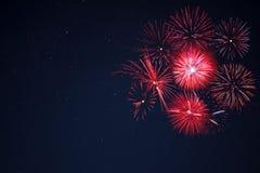 Los fuegos artificiales rojos localizaron al lado derecho sobre el cielo nocturno Fotos de archivo