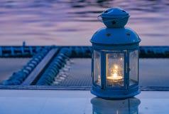 Los fuegos de la vela se contienen en las lámparas, colocadas en la tabla foto de archivo