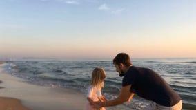 Los funcionamientos de la niña a su padre en la playa y ellos están haciendo girar alrededor blur almacen de video