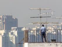 Los funcionarios de un edificio analizan y mantienen las antenas de televisión foto de archivo libre de regalías