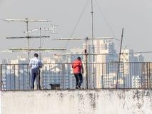 Los funcionarios de un edificio analizan y mantienen las antenas de televisión imagenes de archivo