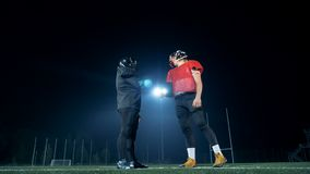 Los futbolistas sacuden las manos mientras que se colocan en uniforme en un campo 4K almacen de metraje de vídeo