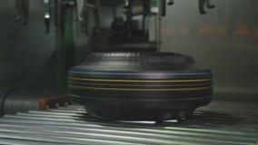 Los ganchos de los estrechos del equipo bajan el neumático en el primer del transportador