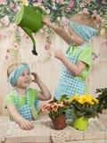 Los gemelos de las muchachas de tres años cuidan para las flores, Imagenes de archivo
