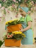 Los gemelos de las muchachas de tres años cuidan para las flores, Fotografía de archivo