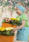 Los gemelos de las muchachas de tres años cuidan para las flores, Fotos de archivo