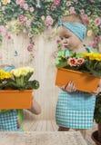 Los gemelos de las muchachas de tres años cuidan para las flores, Imágenes de archivo libres de regalías