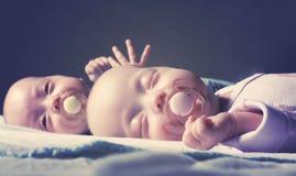 Los gemelos recién nacidos lindos muchacho y muchacha están mintiendo en la cama contra un fondo oscuro Con el tono y empañar foto de archivo
