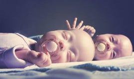Los gemelos recién nacidos lindos muchacho y muchacha están mintiendo en la cama contra un fondo oscuro Con el tono y empañar imagenes de archivo