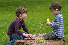 Los gemelos se sientan en el tocón Imagen de archivo libre de regalías