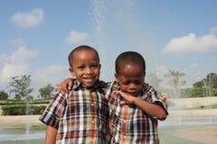 Los gemelos y uno está estornudando Imagenes de archivo