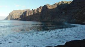 Los Gigantes klippen en het overzien van de oceaan van het strand Ochtend op het Eiland Tenerife Atlantische golven en vulkanisch stock videobeelden