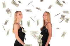 Los gilrs gemelos miran el dólar que cae Fotos de archivo libres de regalías