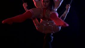 Los gimnastas en traje realizan un truco en el aro aéreo Fondo negro Cámara lenta Cierre para arriba almacen de video