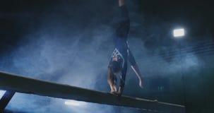 Los gimnastas profesionales de la muchacha de las piernas saltan en la cámara lenta en el humo en el haz de balanza La gimnasia a almacen de video
