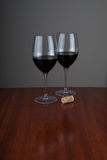 Los glases del vino en brillante woden el fondo Fotografía de archivo