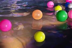 Los globos coloridos en un agua emergen en una piscina foto de archivo