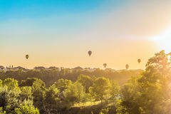 Los globos del aire caliente sobre los tejados de casas suburbanas teniendo en cuenta el sol bajo de la tarde hacen excursionismo Fotografía de archivo libre de regalías