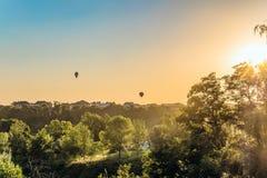 Los globos del aire caliente sobre los tejados de casas suburbanas teniendo en cuenta el sol bajo de la tarde hacen excursionismo Imagen de archivo