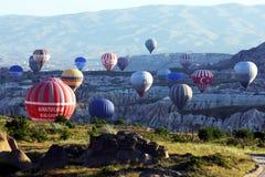 Los globos del aire caliente suben en una onda de Rose Valley mientras que el sol sube cerca de Goreme en la región de Cappadocia Imagen de archivo