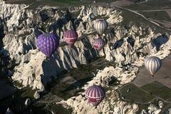 Los globos del aire caliente vuelan sobre el paisaje espectacular de Goreme en la región de Cappadocia de Turquía Imagenes de archivo