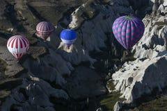 Los globos del aire caliente vuelan sobre el paisaje espectacular de Goreme en la región de Cappadocia de Turquía Imágenes de archivo libres de regalías