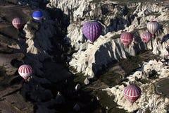 Los globos del aire caliente vuelan sobre el paisaje espectacular de Goreme en la región de Cappadocia de Turquía Fotos de archivo libres de regalías