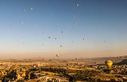 Los globos del aire caliente y el ` s de Cappadocia ajardinan Imagen de archivo
