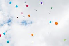 Los globos multicolores con las hojas de arce vuelan en el cielo Fotos de archivo