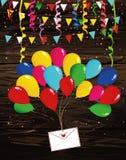 Los globos multicolores del aire aumentan un sobre o una letra con el corazón