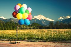 Los globos multicolores golpean festival al aire libre de la vespa con el pie en fondo del cielo azul Fotos de archivo libres de regalías