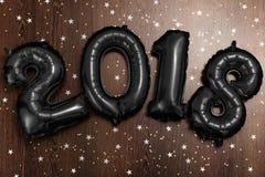 Los globos negros metálicos brillantes figura 2018, la Navidad, globo del Año Nuevo con las estrellas del brillo en la tabla de m Fotografía de archivo libre de regalías