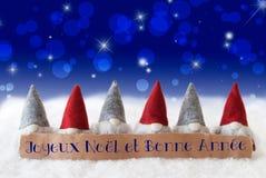 Los gnomos, Bokeh azul, estrellas, Bonne Annee significan Año Nuevo Fotos de archivo