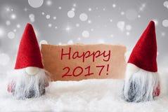 Los gnomos rojos con la tarjeta y la nieve, mandan un SMS a 2017 feliz Foto de archivo