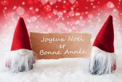 Los gnomos rojos de Christmassy con la tarjeta, Bonne Annee significan Año Nuevo Foto de archivo libre de regalías