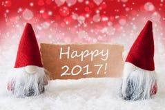 Los gnomos rojos de Christmassy con la tarjeta, mandan un SMS a 2017 feliz Fotos de archivo libres de regalías