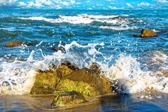 Los golpes de la onda contra la roca y se separan hacia fuera con salpican imagen de archivo libre de regalías