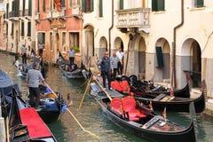 Los gondoleros con las góndolas cuentan con a turistas en Venecia, Italia imagen de archivo libre de regalías