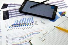 Los gráficos y las cartas de negocio divulgan con la pluma en el escritorio del consejero financiero Concepto financiero de la co fotografía de archivo