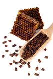 Los gránulos del pan de la abeja y un pedazo de células de la miel se aíslan en un fondo blanco Remedio natural para el aumento d Fotos de archivo