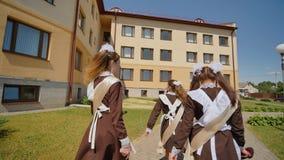Los graduados de la colegiala están caminando a lo largo de la calle Los graduados rusos celebran el día escolar pasado almacen de metraje de vídeo